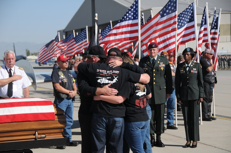The family of Chief Warrant Officer 3 Matthew G. Wagstaff hugs near his casket shortly after his remains arrived at the Utah Air National Guard base in Salt Lake City, Utah, on October 3, 2010. CW3 Wagstaff was a UH-60 Blackhawk pilot who died in Afghanistan September 21. He was serving on his third deployment at the time. (U.S. Air Force photo by Master Sergeant Gary J. Rihn)(RELEASED)