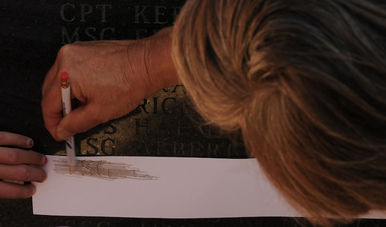 Charlotte, N.C. -- Relatives of deceased airmen of the North Carolina Air National Guard from the past year etch names from the memorial statue onto a keepsake paper after attending a memorial service. (NCANG photo by Tech. Sgt. Rich Kerner)