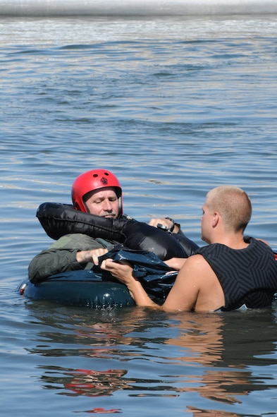 Senior Airman Bo Martz reviews the one-man liferaft with Col. Mathew Jamison during Survival training at Brant Lake, S.D., Aug. 8 2010. (Air Force Photo by Master Sgt. Christopher Stewart, 114th Fighter Wing)
