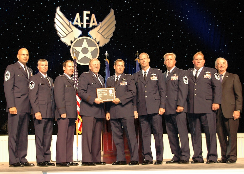 From left:  Chief Master Sgt. Michael Klausutis; Master Sgt. Bruce Callaway; Lt. Col. Timothy Broeking; Lt. Gen. Charles E. Stenner Jr., commander of the Air Force Reserve Command and chief of the Air Force Reserve; Lt. Cols. Daniel Flynn and Thomas Frazier; Senior Master Sgt. Thomas Haddock; Master Sgt. Kevin Woodward; and Joseph Sutter, Air Force Association chairman of the board, are shown at the annual AFA awards ceremony at National Harbor, Md. in September. General Stenner and Mr. Sutter joined the Duke Field reservist aircrew members on stage as they were presented the AFA's 2009 Lt. Gen. William H. Tunner award for the Air Force's most outstanding airlift aircrew .  Crew members not shown:  Lt. Col. Steven Jensen and Capt. Miriam Williams. (U.S. Air Force photo/Dan Neely)