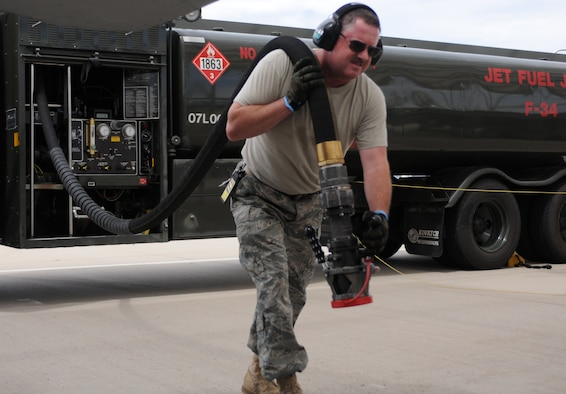 Staff Sgt. Buzz Decker drags a fuel hose from a 6,000-gallon tanker to an F-16 on the 162nd Fighter Wing flightline at Tucson International Airport; a process that is repeated nearly 1,200 times each month. (Air Force photo by Staff Sgt. Jordan Jones)