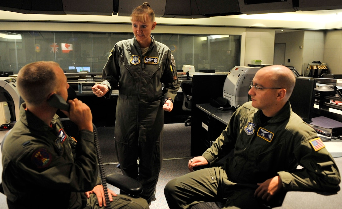 BUCKLEY AIR FORCE BASE, Colo. -- Lt. Col. Jennifer Jenkins, 2nd Space Warning squadron commander, receives information from 1st Lt. Brian Yoakam, 2 SWS, and Staff Sgt. Jered Klodt, 2 SWS. The 2nd and 8th SWS provide continuous and reliable warning of attack of North America and the U.S. and her allies worldwide. The organization is comprised of mission partners from Canada, Great Britain and Australia and has both active duty and reserve U.S. Air Force members. (U.S. Air Force Photo by Airman 1st Class Paul Labbe.)