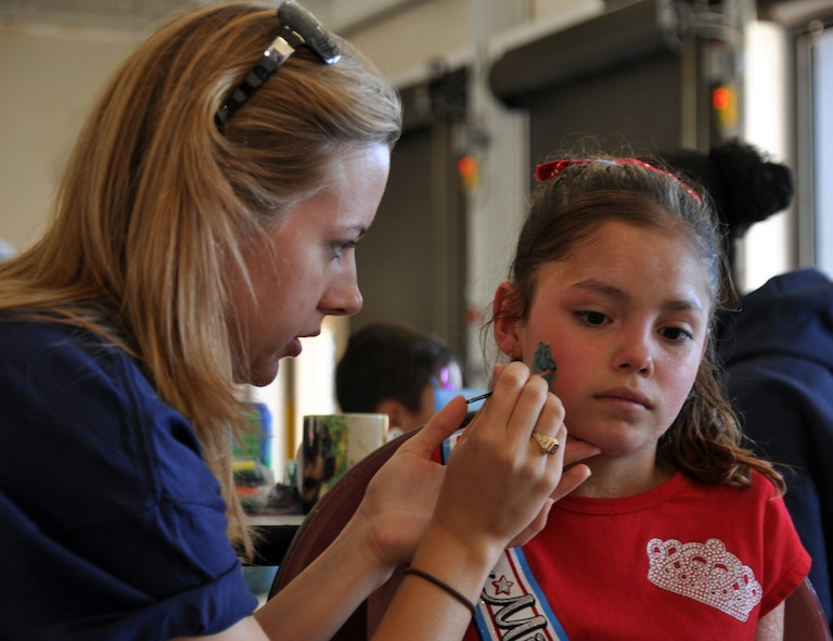 Second Lt. Sara Greco, 14th Mission Support Group and Fire Prevention Week Open House volunteer, paints the face of a young attendee at the event Oct. 2. (U.S. Air Force photo/Airman 1st Class Chase Hedrick).