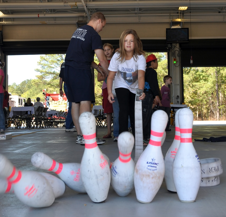 Alyssa Franks, daughter of Staff Sgt. Bryan Franks, knocks over pins while bowling with a fire hose at the 2010 Fire Prevention Week Open House Oct. 2.(U.S. Air Force photo/Airman 1st Class Chase Hedrick)