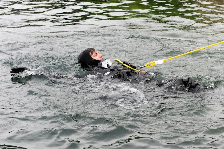 STONEY COVE, England – Senior Airman Eli Reynolds, 56th Rescue Squadron pararescueman, pulls tension on the line while surface swimming to his descent point for subsurface search, rescue and recovery training Oct. 5. Before descending, dive instructors observe the diver for possible bubbles in their air manifolds. (U.S. Air Force photo/Airman 1st Class Lausanne Morgan)