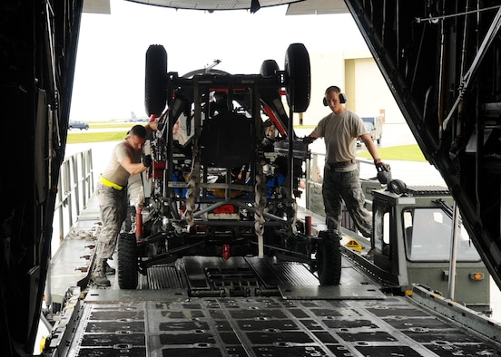 Airman 1st Class James Weimer and Staff Sgt. Allen Rees, 734th Air Mobility Squadron aerial porters, load equipment used for Valiant Shield 2010 on a C-130 Hercules at Andersen Air Force Base, Guam, Sept. 30. (U.S. Air Force photo/ Senior Airman Nichelle Anderson)