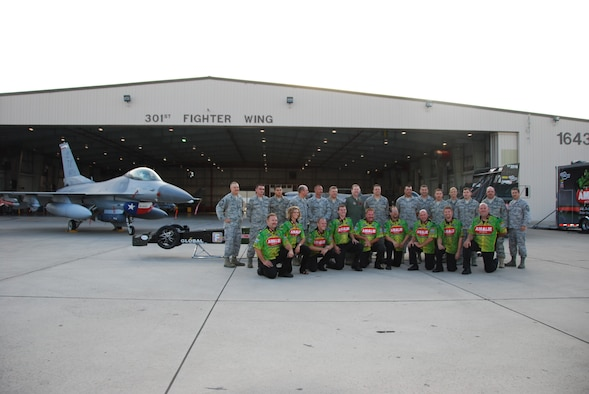 Driver of the Amalie Oil Top Fuel dragster, Mr. Terry McMillen and his team join their counterparts in the 301st Fighter Wing Maintenance Group. McMillen and his crew recently visited the 301st Fighter Wing before racing at a Dallas-area event. (Air Force Photo/Tech. Sgt. Shawn McCowan)