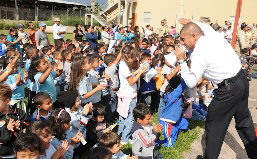 SOTO CANO AIR BASE, Honduras --   Mr. Herberth Gaekel, a civilian fire inspector with the 612th Air Base Squadron fire department here, has Comayagua school children wave good-bye to Sparky the Fire Dog during a National Fire Prevention Week event here Oct. 6. Local children and firefighters visited the base fire department to learn about fire fighting tools and fire prevention. (U.S. Air Force photo/Capt. John Stamm)