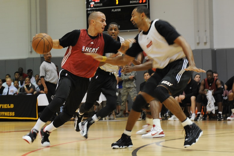 Carlos Arroyo, Miami HEAT guard, attempts to drive past Juwan Howard, during the 2010 Training Camp scrimmage at the Aderholt Fitness Center at Hurlburt Field, Fla., Oct. 1, 2010. The HEAT took time out from their training camp to display their skills in front of more than 500 Hurlburt and Eglin Air Force Base Airmen, DoD civilians, and dependents. (DoD photo by U.S. Air Force Senior Airman Sheila deVera/RELEASED)