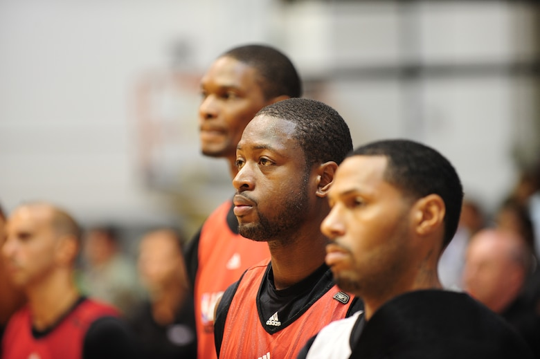 Miami HEAT players (Left to Right) Chris Bosh, Dwyane Wade and Eddie House stand for the singing of the National Anthem at the Aderholt Fitness Center, Hurlburt Field Fla. Oct. 1, 2010. The HEAT took time out from their training camp to display their skills in front of more than 500 Hurlburt and Eglin Air Force Base Airmen, DoD Civilians and dependents. (DoD Photo by Staff Sgt. Stephanie Jacobs/RELEASED)