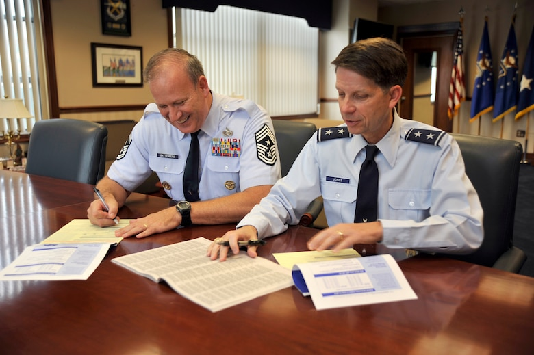Maj. Gen. Darrell Jones, Air Force District of Washington commander, and Chief Master Sgt. Pat Battenberg, AFDW command chief, fill out their Combined Federal Campaign forms at Joint Base Andrews, Md., Oct 1.  CFC is the world's largest and most successful annual workplace charity campaign, with more than 300 CFC campaigns throughout the country and internationally to help to raise millions of dollars each year. (U.S. Air Force photo by Staff Sgt. Christopher A. Marasky)