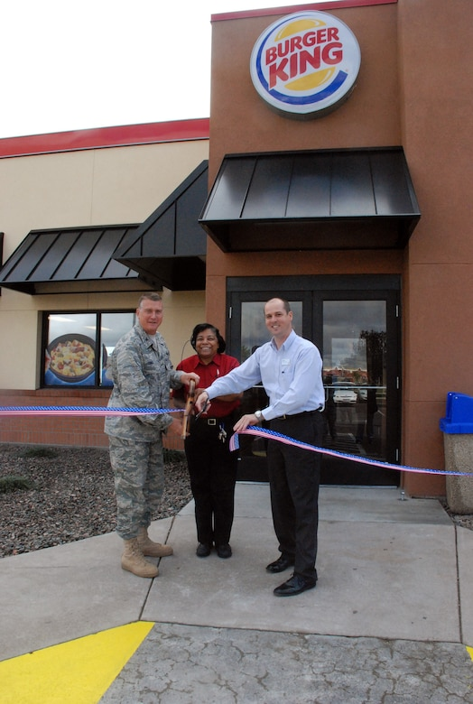 Colonel Greg Tims, 90th Missile Wing commander, Desiree Taylor, Burger King manager and Jeff Hyatt, AAFES Regional Manager, cut the ribbon for F. E. Warren's reopening of Burger King here on Tuesday.  The base eatery was closed for about 90 days due to renovations, several of which included a new spacious dining room and more efficient kitchen space. (U.S. Air Force photo by 1st Lt. Brooke Brzozowske)