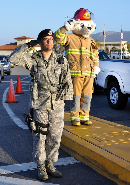 Senior Airman Pablo Castillo, 452nd Security Forces Squadron, and Sparky (played by Staff Sgt. Jarod Bernard, March Fire Department) observe morning colors at the main gate Oct. 7 with a salute. Sparky and fire department staff were at the gate to hand out flyers to drivers during the morning rush. (U.S. Air Force photo by Master Sgt. Linda Welz)
