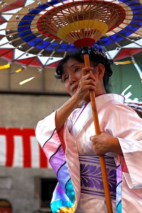 A festival performer dances down the street with a decorative umbrella during the closing parade of the 54th annual Iwakuni Festival hosted in the downtown area by the train station Sunday. Various clubs from around the station also participated in the closing parade dressed in traditional yukatas or decorative costumes.