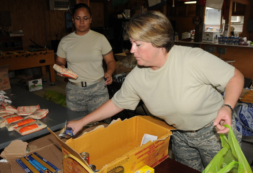 SOTO CANO AIR BASE, Honduras --  Master Sgt. Danielle McClarin (right) and Tech. Sgt. Diora Farrar, both with the Medical Element here, help to pack bags full of food and other supplies Oct. 15 in preparation for the Chapel Hike. Team Bravo members volunteer to help the Soto Cano Air Base Friendship Chapel deliver supplies to remote villages. (U.S. Air Force photo/Capt. John Stamm)