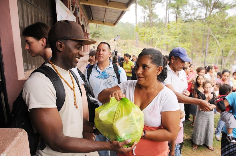 SAN JERONIMO, Honduras --  Staff Sgt. Joel Hart, with Joint Task Force-Bravo, hands a bag of food and other supplies to a local woman during a Chapel Hike here Oct. 16. Besides handing out supplies, Team Bravo members visited with the villagers and provided games for the children. (U.S. Air Force photo/Tech. Sgt. Benjamin Rojek)