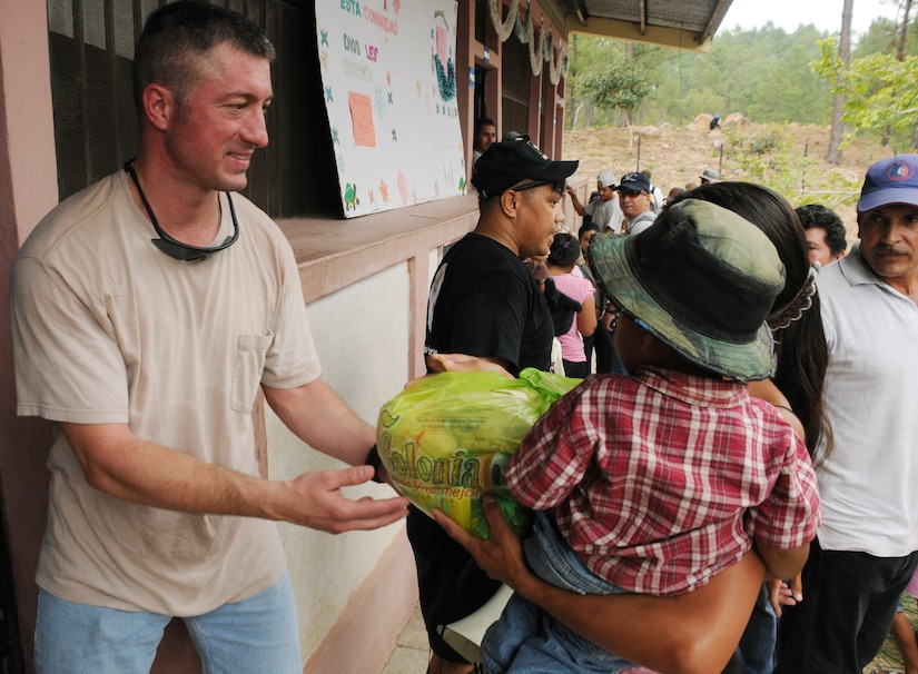 SAN JERONIMO, Honduras --  Greeting a woman and her child, Capt. John Stamm, with Joint Task Forc-Bravo, hands off a bag of food and other supplies during the Chapel Hike here Oct. 16. The Soto Cano Air Base Friendship Chapel sponsors monthly hiking trips that partners JTF-Bravo members with local community leaders, city hall officials and the World Food Program to provide support to surrounding villages in need of food and supplies. (U.S. Air Force photo/Tech. Sgt. Benjamin Rojek)