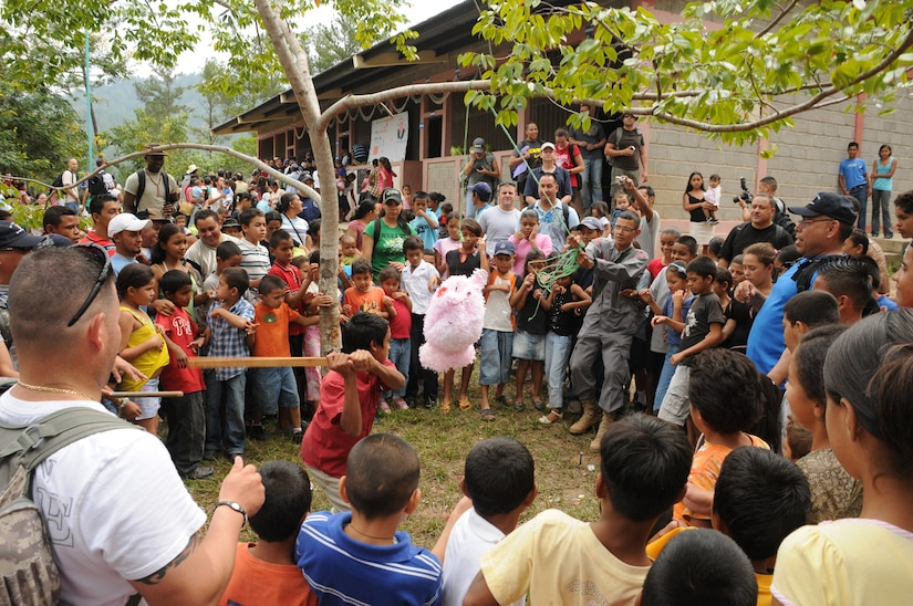 SAN JERONIMO, Honduras --  With help from local firemen and Joint Task Force-Bravo members, children in this remote village get to take a swing at a pinata here Oct. 16 during the Chapel Hike. More than 70 Team Bravo members hiked more than two miles to the village to deliver food and other goods. (U.S. Air Force photo/Tech. Sgt. Benjamin Rojek)