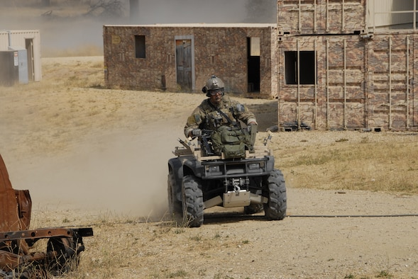 A pararescueman from the 131st Rescue Squadron rides an ATV through an urban assault course during a hostage recovery scenario as part of exercise Soaring Angel 10-2 Oct. 1, 2010 at Fort Hunter Liggett, Calif. Soaring Angel is the 129th Rescue Wing's tactical training exercise that prepares Airmen for an upcoming Operational Readiness Inspection. (Air National Guard photo by Airman 1st Class Jessica Green)