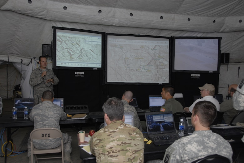 Maj. Mathew Wenthe, the assistant director of operations for weapons and tactics with the 129th Rescue Squadron, briefs members of the Rescue Operations Center at the forward operating base set up for exercise Soaring Angel 10-2 at Fort Hunter Liggett, Calif. Oct. 2, 2010 about the hostage recovery scenario being conducted by members from the 129th Rescue Squadron's HH-60G Pave Hawk rescue helicopter teams, the 130th Rescue Squadron C-130P Combat Shadow crews and the 131st Rescue Squadron's guardian angel players. Soaring Angel is the 129 Rescue Wings tactical training exercise in preparation for their upcoming Operational Readiness Inspection in Dec. 2011. (Air National Guard photo by Airman 1st Class Jessica Green)