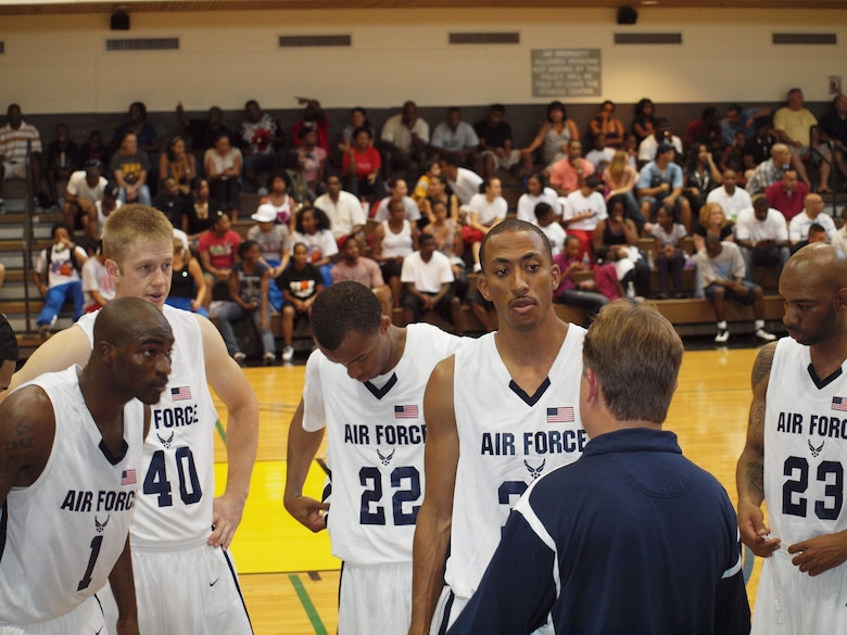 James Lewis, a Senior Airman with the 460th Comptrollers Squadron, stands in the huddle (left) during the Armed Forces Basketball Tournament. Lewis, who played professionally for four years in Germany, helped the team to it's fourth championship in as many years. (Courtesy photo)
