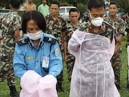 Nepalese medical personnel practice donning/doffing personal protective equipment to control the spread of infectious pathogens during DIMO's avian/pandemic influenza course; Kathmandu, Nepal, June 2010.  (US Air Force Photo)