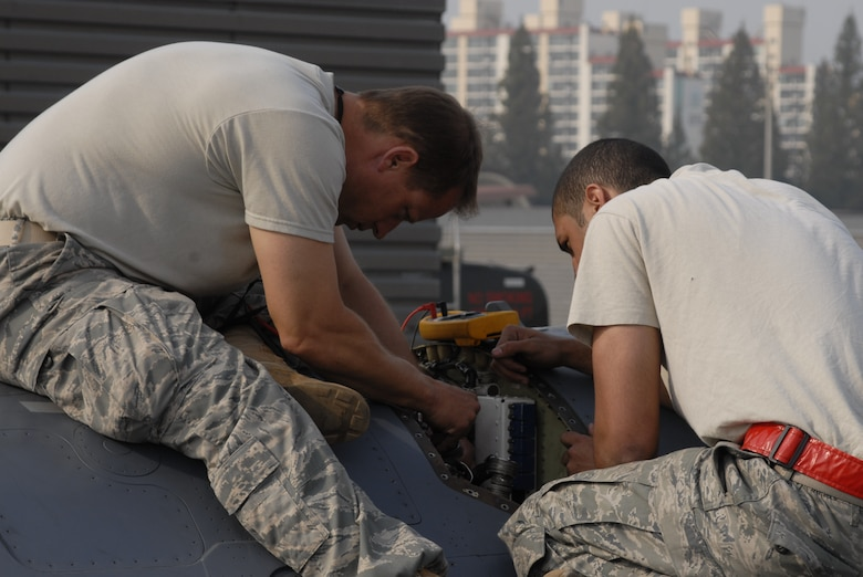 Maj. Daniel Mattioda, 8th Maintenance Squadron, left, and Staff Sgt. Matthew Wilkerson, 51st Aircraft Maintenance Squadron, troubleshoot an electrical system problem in an Osan F-16 Fighting Falcon Oct. 20 during exercise Max Thunder 10-2 at Kwangju Air Base, Republic of Korea. Major Mattioda is prior-enlisted with an electrical environmental background. (U.S. Air Force photo/Staff Sgt. Eric Burks)