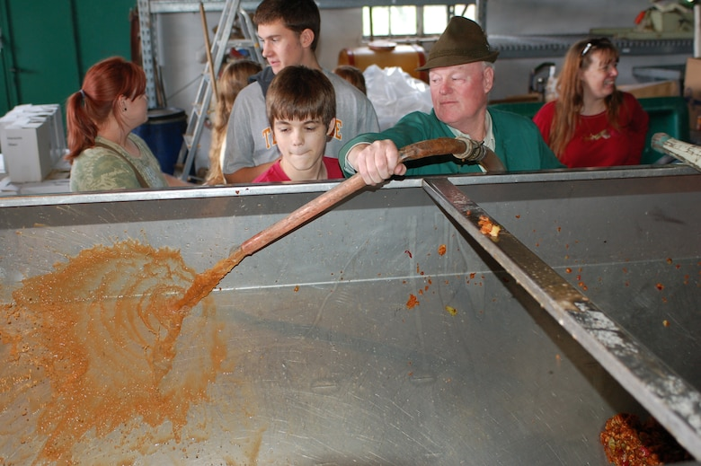 OSANN-MONZEL, Germany--Children from the Spangdahlem Homeschooling Group observe how the vintner, Matthias Sailer rinses out the apple trailer with juice and a steam hose. Together with their parents, children from the Spangdahlem Homeschooling Group recently visited the local Sailer-Cipolla winery in Osann-Monzel, helped vintners collect apples and learned how to make apple cider. (U.S. Air Force photo/Iris Reiff)