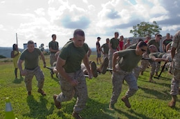 Marines with Headquarters and Service Battalion, U. S. Marine Corps Forces, Pacific supply take off during a stretcher carry race during the family day and field meet at Bordelon Field Oct. 22. Sections were split up into teams and competed in several events, including pugil sticks, egg toss and tug-of-war.