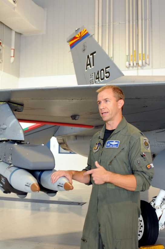 Lt. Col. Todd Seger, test pilot and combined test force director for the Air National Guard, Air Force Reserve Command Test Center, talks about new small diameter, laser guided bombs added to an early model Block 30 F-16 Fighting Falcon at the Weapons and Tactics Conference in Tucson, Ariz., Oct. 20. The test center hosted scores of Guard and Reserve warfighters during the conference to gather input for improving the capability of legacy aircraft. (US Air Force photo/Maj. Gabe Johnson)