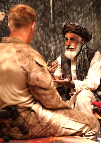 """U.S. Marine First Lt. Taylor Williams, platoon commander for Weapons Platoon, Fox Company, 2nd Battalion, 6th Marine Regiment, speaks with a village elder about establishing a neighborhood watch under the Interim Security Critical Infrastructure program, in Marjah, Oct. 23, 2010. """"When we first came in, we took contact every day for about the first two and-a-half months. The conditions were not stable enough for a [citizen-run] security program in the northern part of our area,"""" said Williams, 24, from Raleigh, N.C. """"Now it seems like the locals are ready to sustain their own type of police force here. The security situation has changed significantly down here."""""""