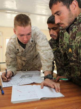 Sgt. Michael Mondt, the lead instructor with the Regimental Combat Team 1 Embedded Training Team, shows Afghan National Army Staff Sgts. Baz Mir and Noordin how to plot points on a six-digit grid, Oct. 23, during the first ANA instructor course at Camp Dwyer, Afghanistan. Mondt is from Winnemucca, Nev.