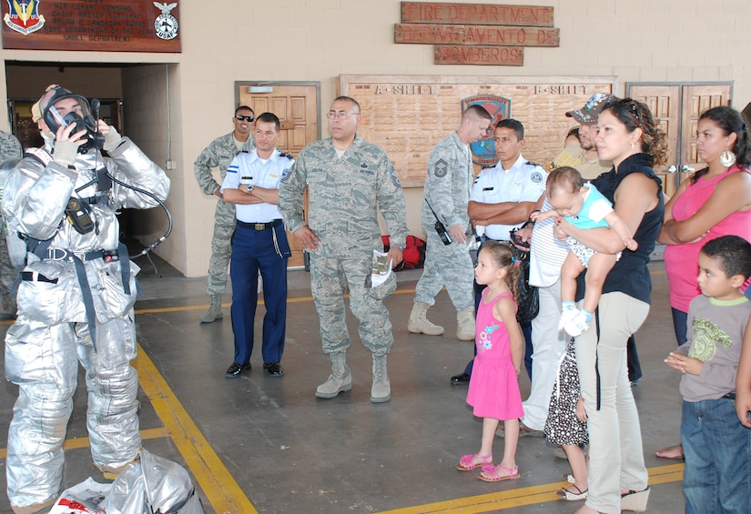 SOTO CANO AIR BASE, Honduras --  A 612th Air Base Squadron firefighter (left) demonstrates putting on a protective fire suit as part of a tour of the fire department during Foreign Service National Family Day here Oct. 22. FSNs and their family members also visited the 1-228th Aviation Regiment and the Honduran Air Force Academy, among other places on Soto Cano. (U.S. Air Force photo/Capt. John Stamm)