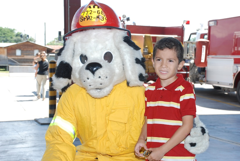 SOTO CANO AIR BASE, Honduras --  The child of a foreign service national here poses with Sparky the Fire Dog during FSN Family Day here Oct. 22. FSNs and their families were treated to a tour of base facilities, to include the Soto Cano Fire Department. (U.S. Air Force photo/Capt. John Stamm)