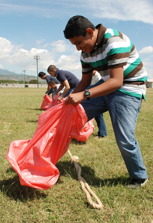 SOTO CANO AIR BASE, Honduras --  Family members and foreign service nationals participate in a sack race during FSN Family Day here Oct. 22. Throughout the day, FSNs and their family members toured base facilities, played games, and were given service awards. (U.S. Air Force photo/Capt. John Stamm)