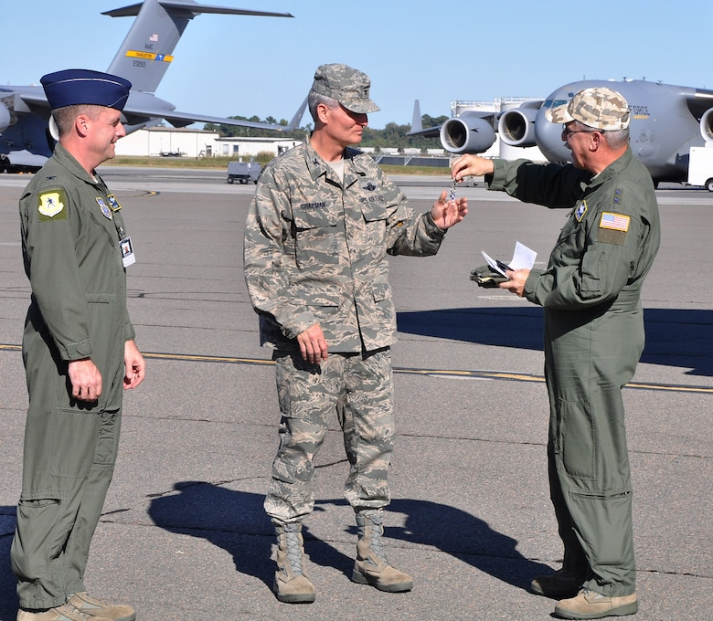 Major General Martin Mazick (right), vice commander for the Air Force Reserve Command, presents Colonel Steven Chapman (center), commander of the 315th Airlift Wing, the symbolic keys to the newest C-17 arriving at Joint Base Charleston.  Maj. Gen. Mazick and Col. Chapman are joined by Col. John Wood, commander of the 437th Airlift Wing (U.S. Air Force photo/Staff Sgt. Shane Ellis)