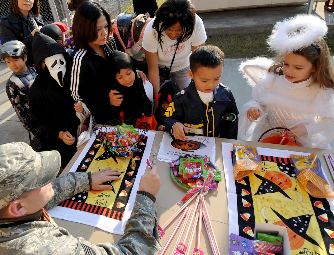 Children gather around candy booths at the second annual Osan Trick-or-Treat Bash Oct. 28. Candy was handed out through a safe maze of offices and booths from military personnel and base organizations. The Trick-or-Treat Bash was followed by a costume contest at the Officers club. (U.S. Air Force Photo/Senior Airman Evelyn Chavez)
