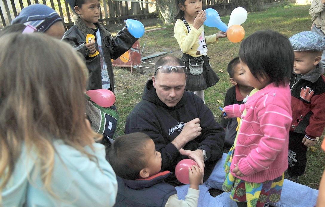 Tech. Sgt. Joe Corder fills balloons for kids Oct. 18, 2010, at the Solnyshko school near Vasilievka, Kyrgyzstan. Several Airmen who are deployed to the Manas Transit Center, Kyrgyzstan, visited the school to deliver cold weather items and spend time with the kids. (U.S. Air Force photo/Staff Sgt. J.G. Buzanowski)