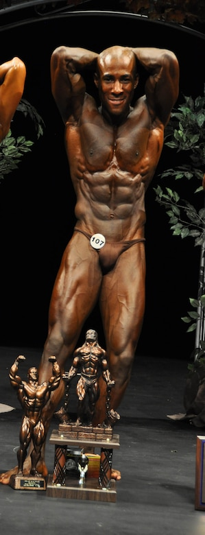 Staff Sgt. Eric Schmidt, 27th Special Operations Civil Engineer Squadron, stands behind his trophies after being awarded first place in the Organization of Competitive Bodybuilders Arizona Natural Bodybuilding and Figure Pro Qualifier Competition. Sergeant Schmidt won first place in his division and first overall to win a Pro-card allowing him to compete in International Fitness and Physique Association professional competitions. (Courtesy photo)
