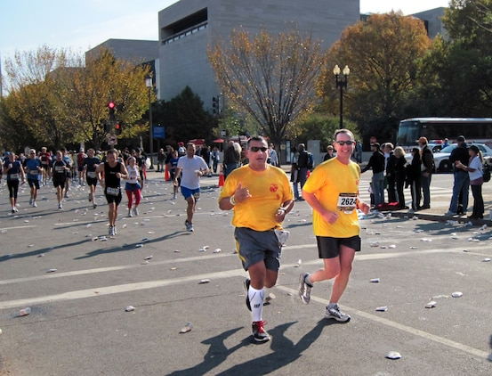 Gunnery Sergeant John Caraway (left), who works in Marine Corps Systems Command's Communications, Intelligence and Networking Systems, runs alongside retired Lieutenant Colonel Bill Rysanek in the Marine Corps Marathon on Oct. 31. Caraway was diagnosed with cancer in April.