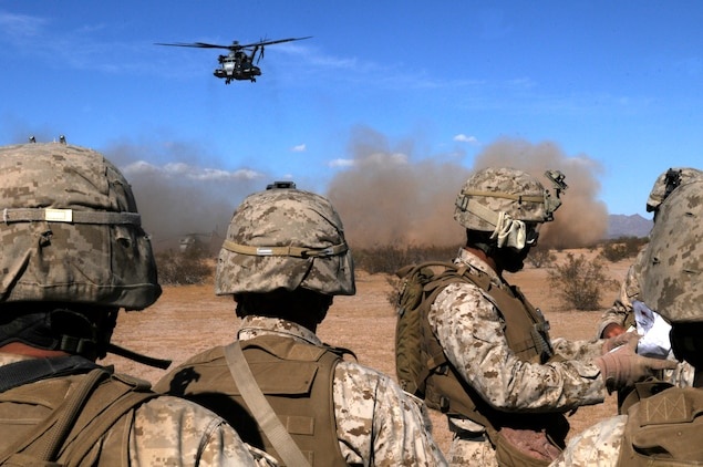 Marines with E Company, 2nd Battalion, 7th Marine Regiment, watch a CH-53E Super Stallion take off while being briefed on the mission by 1st Sgt. Rogello Haro, E Company first sergeant, during the final exercise of the recent Weapons and Tactics Instructor course at Auxiliary Airfield 6 on the Barry M. Goldwater Range in Ariz., Oct. 30, 2010. Operation War Wagon tested the skills attained by the WTI students and included the participation of approximately 250 infantry Marines from the battalion.