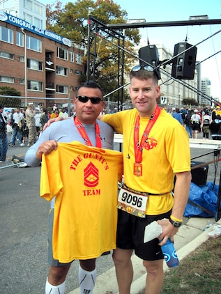 Gunnery Sergeant John Caraway (left), who was diagnosed with cancer in April, holds up his support team's shirt with Major Brian Rideout at the Marine Corps Marathon on Oct. 31.