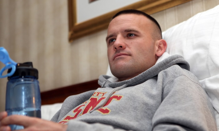 """Relaxing on his hotel bed, Capt. Richard Jennings watches TV at about 5 a.m. Oct. 31, three hours before the start of the 35th annual Marine Corps Marathon. """"I woke up, ate some oatmeal, a banana and a bagel with some peanut butter on it,"""" Jennings said. """"I'm feeling good and rested."""""""