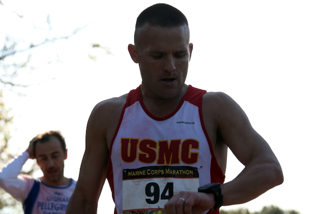 """Capt. Richard Jennings checks his watch to see his time just after crossing the finish line of the 35th annual Marine Corps Marathon Oct. 31, 2010. His time read, 2 hours, 36 minutes and 20 seconds, a personal best time by 2 minutes and 40 seconds, despite some extra time off due to a bad hip. """"My hip worked out well,"""" Jennings said. """"I felt a little weak in the beginning, a little sluggish from the time off, but today everything went well."""""""