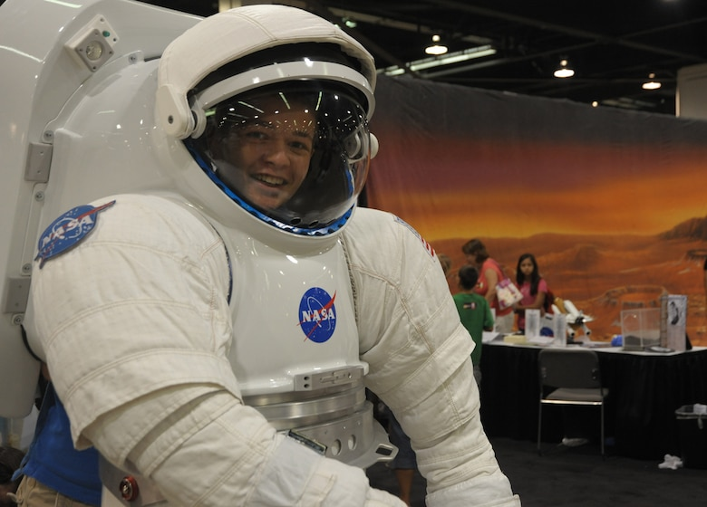 A future astronaut tries on a spacesuit in Education Alley at the AIAA Space 2010 conference, Sept.1.  (Photo by Joe Juarez)