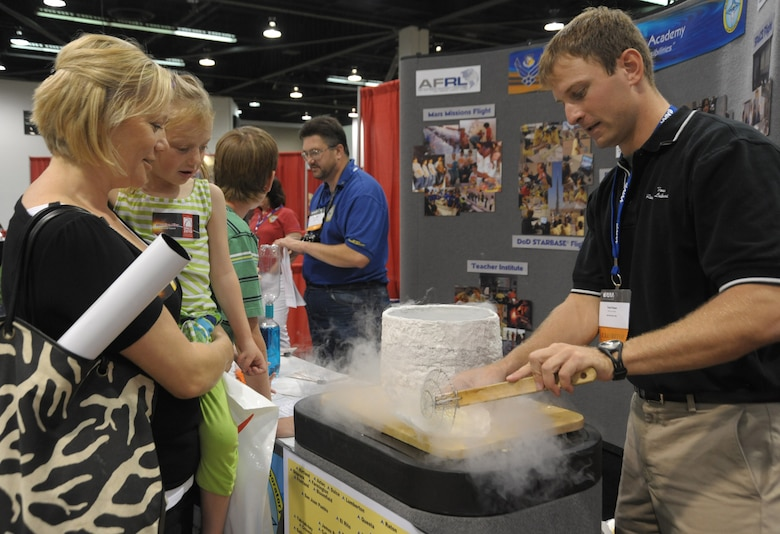 A staffer from the Air Force Research Laboratory demonstrates  a science experiment freezing items in liquid nitrogen in Education Alley at the AIAA Space 2010 conference, Sept.1.  Staff from various government agencies and industry partners demonstrated science and space exploration to students visiting the conference. (Photo by Joe Juarez)