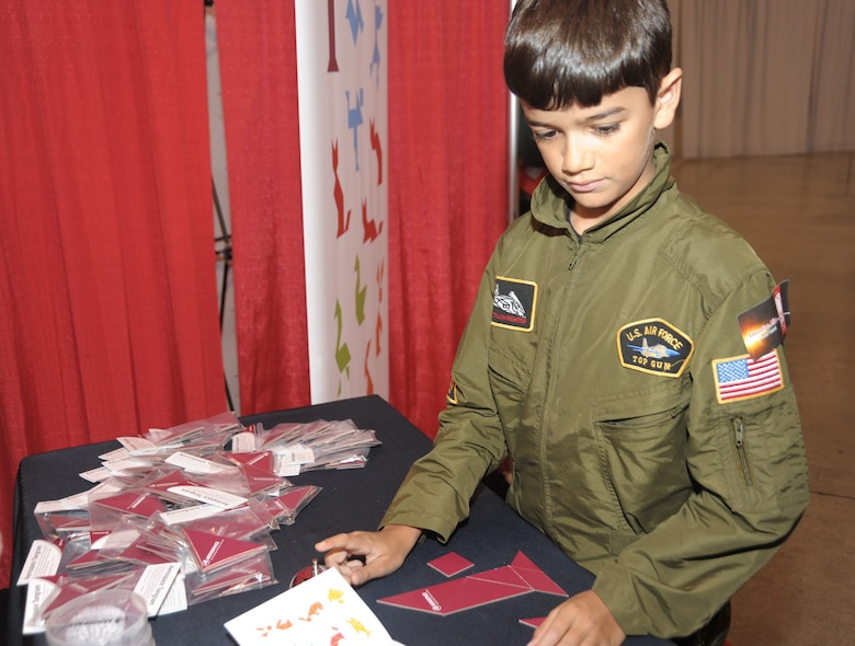 A future Airman builds a rocket out of puzzle pieces at the jointly manned SMC and Aerospace Corporation booth in Education Alley at the AIAA Space 2010 conference, Sept.1.  The puzzle is called a tangram, which consists of seven flat pieces used to form shapes. (Photo by Joe Juarez)