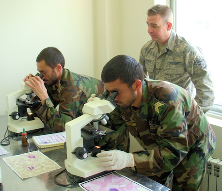 KABUL, Afghanistan -- Staff Sgt. Cole Mason, a medical embedded training team member, provides Afghan students in the Allied Health Professional's Institute near Camp Eggars, Afghanistan, hands-on instruction with microscopes. Sergeant Mason instructed a class of 20 Afghan National Guard and Afghan National Police for six months regarding laboratory procedures and practices. (Air Force courtesy photo)