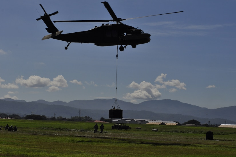 SOTO CANO AIR BASE, Honduras --  Members of Army Forces here stay at a safe distance as a UH-60 Blackhawk helicopter lifts cargo during the bi-monthly sling load training here Sept. 1. ARFOR members learn to rig loads to both a UH-60 and CH-47 Chinook helicopter. (U.S. Air Force photo/Martin Chahin)