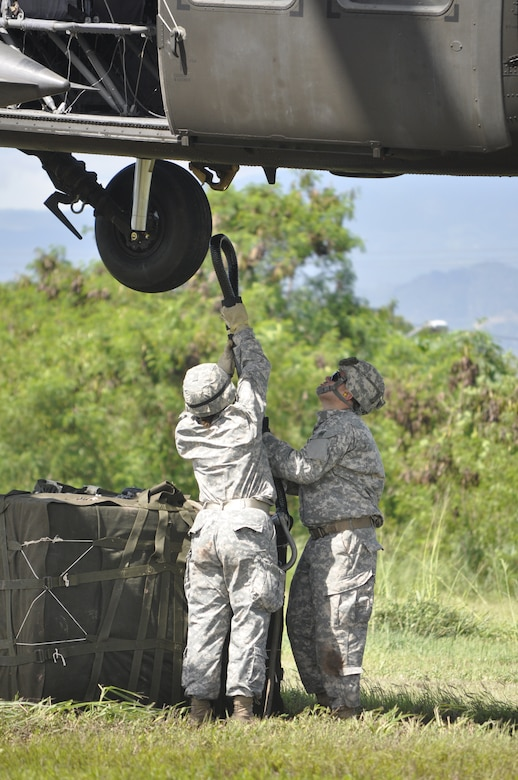 SOTO CANO AIR BASE, Honduras --  Spc. Peggi Williams, left, with J4, and Staff Sgt. Eugenio Gonzalez, with Army Forces, work to hook cargo to a helicopter during sling load training here Sept. 1. In case of humanitarian or disaster relief efforts to areas not accessible by convoy, ARFOR personnel will rig cargo to helicopters for transport. (U.S. Air Force photo/Martin Chahin)